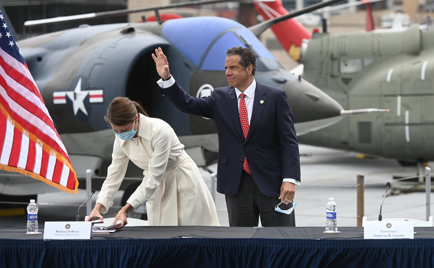 Gov. Andrew Cuomo waves to reporters after finishing his daily coronavirus briefing Monday from the USS Intrepid Sea Air & Space Museum on Manhattan's Pier 86.