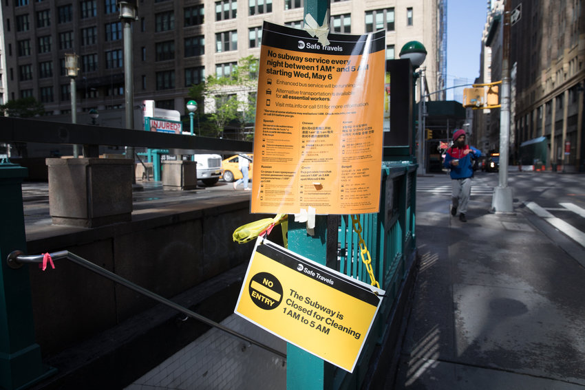 Signs inform passersby of the overnight closure of the subway system beginning at 1 a.m., which not only has made trips by 'essential' commuters more difficult, but has also displaced hundreds of homeless people who have found the subway to be a sort of overnight shelter.