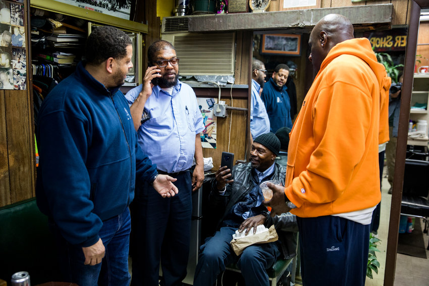 Walter Watson, second from left, talks on the phone inside Marble Hill's International Unisex Salon on March 6, where he was a longtime customer. The MTA bus driver would die from complications related to COVID-19 less than two months later at 55.