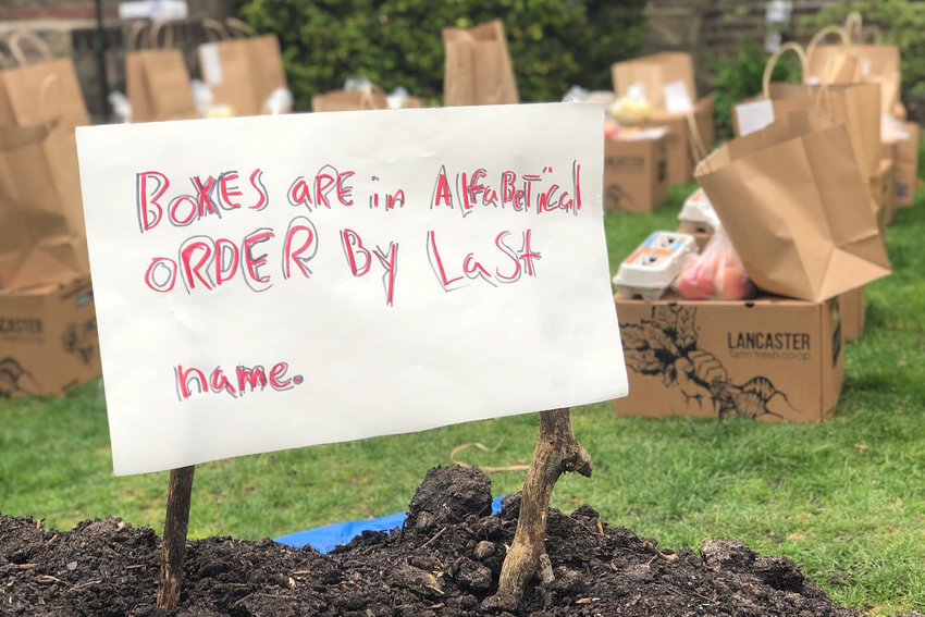 A sign informs customers that 'farm boxes' are organized alphabetically by last name. Moss Cafe owner Emily Weisberg has kept business alive by continuing to buy from the farms she used when her cafe was open, except now she's selling produce directly to people.