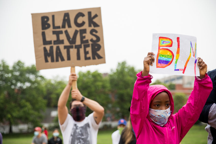 Mourners hold up signs in support of the Black Lives Matter movement at a vigil in Seton Park remembering African Americans killed by police brutality.