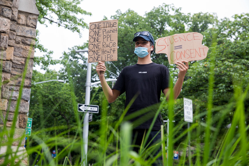 James Cortez holds signs advocating for equality and action in the face of police brutality during an ongoing vigil at the Riverdale Monument that was organized following the police-involved death of George Floyd in Minneapolis.
