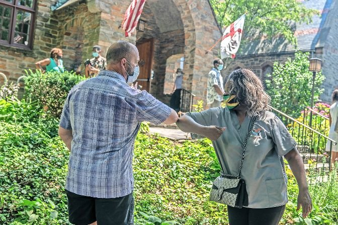 Father Andrew Butler and a parish member say goodbye by bumping elbows during Butler's farewell parade in front of Christ Church Riverdale on July 12. Butler is now on his way to Palm Springs, California.