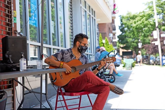 Sinhué Padilla Isunza, a Bronx resident and career musician, performs on Johnson Avenue on Aug. 2, as part of the first Open Streets Sundays. The program, run by the Kingsbridge Riverdale Van Cortlandt Development Corp., blocks off streets so restaurants and artists can set up stands in a socially distanced manner.