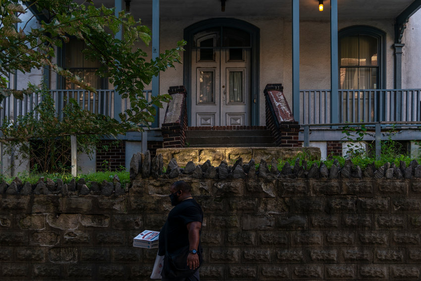 A person walks past 3029 Godwin Terrace with a pair of pizzas in hand, creating a much different streetscape than what the Moller family saw when they first moved in back in 1870.