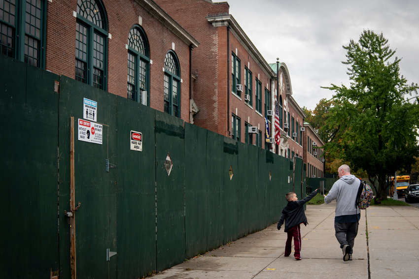 A father and son walk past P.S. 81 Robert J. Christen. Public school parents face a difficult decision in the upcoming days — should they opt for hybrid learning? If not, their children will remain remote for the rest of the academic year.