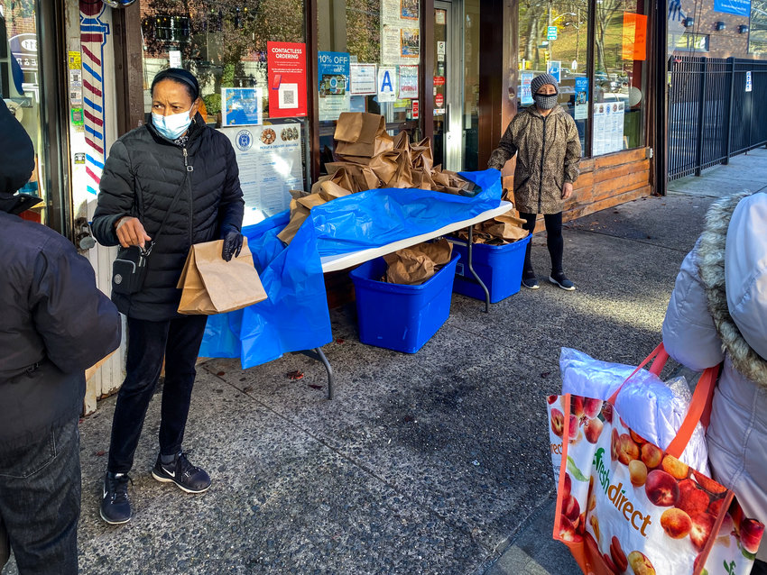 Antonia Feliz works with another volunteer to hand out bags of food in front of Taste & Sabor on West 231st Street to those who might be a little short on food. The restaurant has been lending a helping hand to those in need even before the coronavirus pandemic.