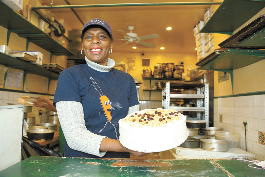 Betty Campbell-Adams, owner, at Lloyd's Carrot Cake, showing one of her prize creations at the store's 30th anniversary in 2016.