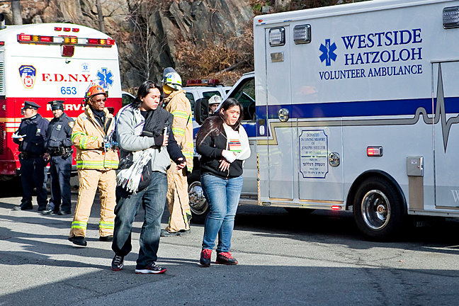 Victims of the Metro-North derailment near the Spuyten Duyvil station on Dec. 1, 2013, walk toward an ambulance on Edsall Avenue.