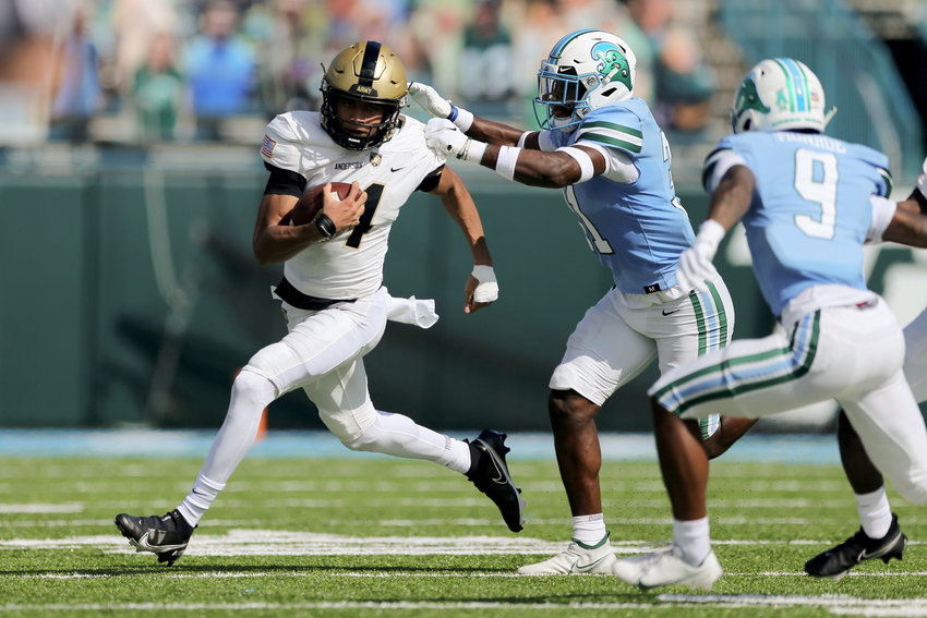 Army quarterback Christian Anderson tries to break loose from defenders in a November college football game against Tulane. Anderson helped West Point to a 9-3 record, culminating in a 24-21 loss against West Virginia in the AutoZone Liberty Bowl.