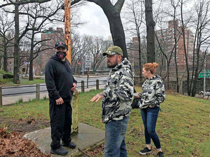 Tree Army owner Nicholas Lynch and wife Joelle check out the status of the old flagpole near the Riverdale Monument on West 239th Street with Danny Monge. The three are putting together a small group they hope can restore the flagpole and have the stars and stripes flying on top of it in time for Flag Day in June.