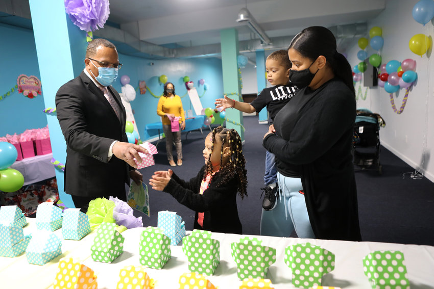 Andre Coleman, the program director at the Broadway Family Plaza transitional housing facility gives a cupcake to Karla's children, McKenzly and McKayson, during a Mother's Day event last week. The event was part of a produce drive organized by Kingsbridge Unidos, a mutual aid group ensuring families get fresh vegetables in this part of the Bronx.