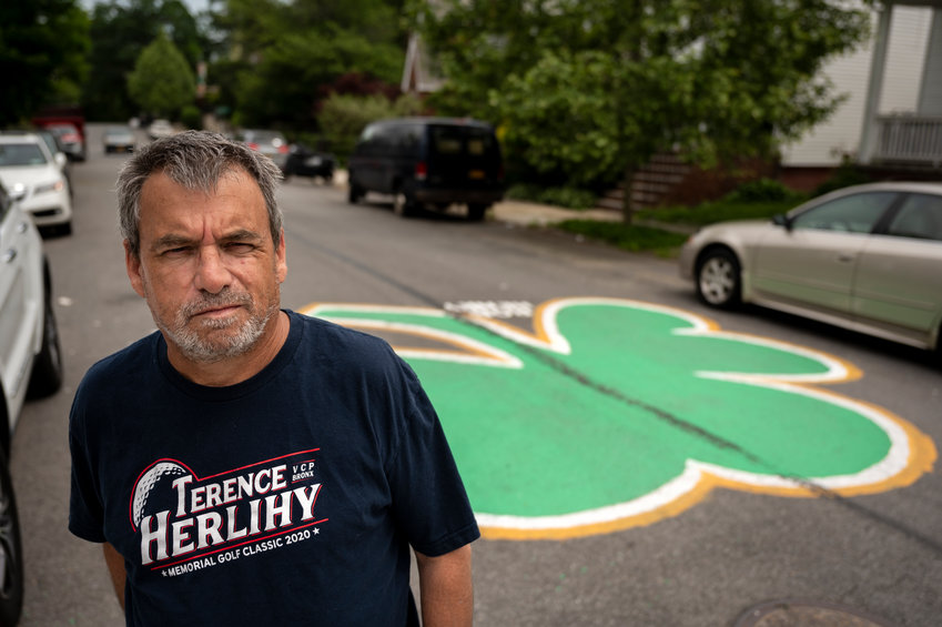 Pat Connaire poses for a portrait near the clover he painted at the intersection of West 260th St and Delafield Ave to honor two recently deceased Bronxites.