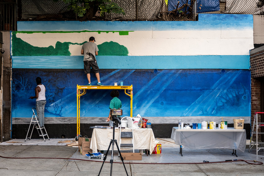 Artist Nicky Enright joins a volunteer painting a mural on the back retaining wall of 3636 Greystone Ave., where he lives. Enright was commissioned to paint this mural, 'Aquarium,' by his building's co-op board because he's no stranger to mural painting.