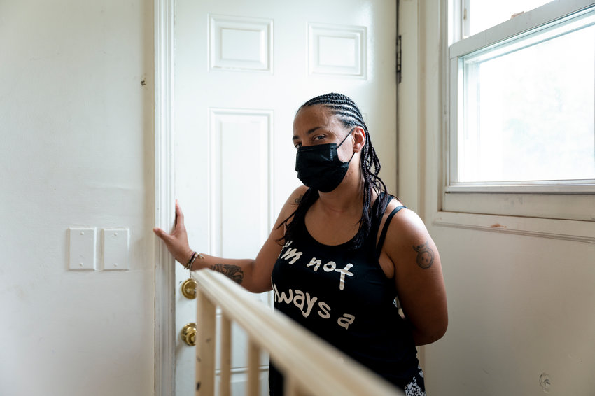 Veronica Cruz stands in the doorway of her mother's Bronx apartment. Cruz — like many other families — is waiting to hear whether she's eligible for federal rental assistance dollars she applied for months ago. The state has $2.6 billion to distribute, but little has so far made it renters in need.