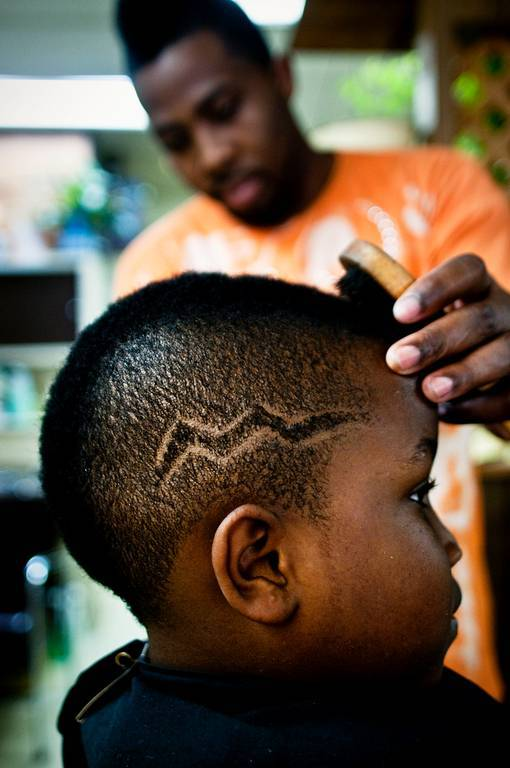 Barber Craig Butler gives his little brother Antwone a lightning bolt buzz.