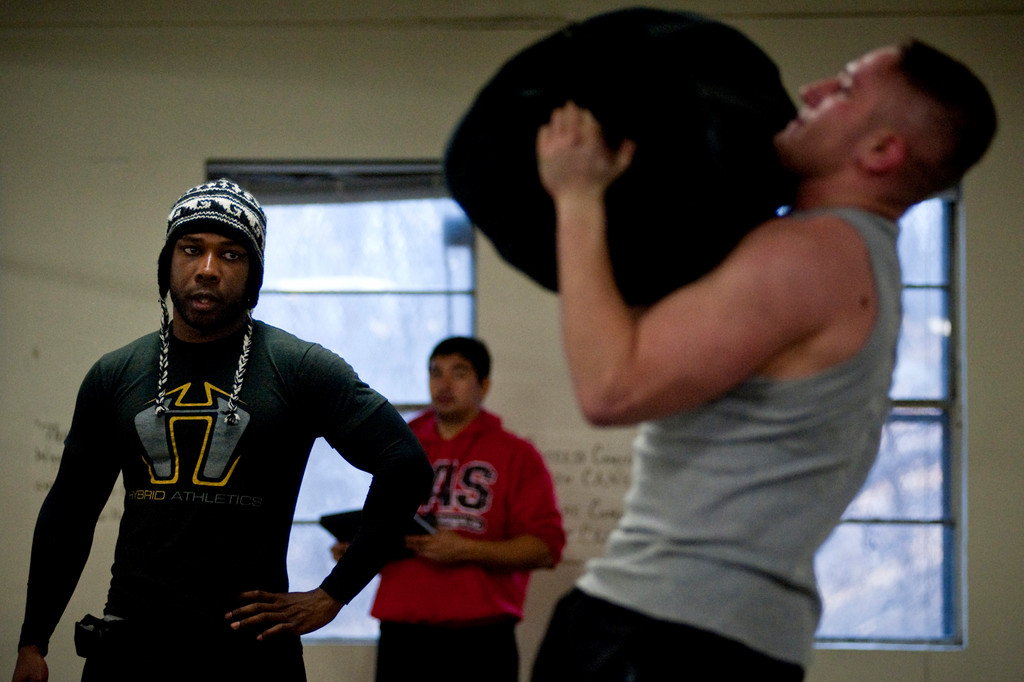 CrossFit Riverdale trainer Will Harris, left, watches as competitor Ben Kaminski lifts a 90 lb sandbag over his head.