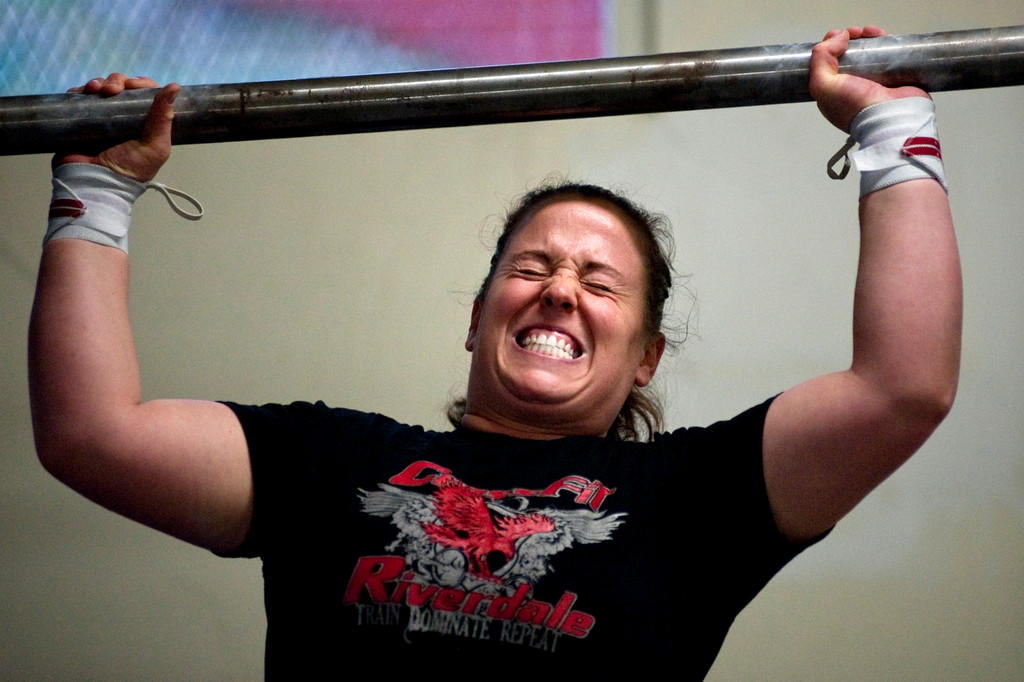 Celestine Calpin of Riverdale lifts a 90 lb axle over her head during Sunday's   CrossFit Riverdale-hosted charity strongest man and woman event on Dec. 13.