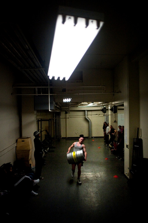 Ben Kaminski carries a  160 lb keg across the gym as he competes in the sandbag and keg-carrying medley.