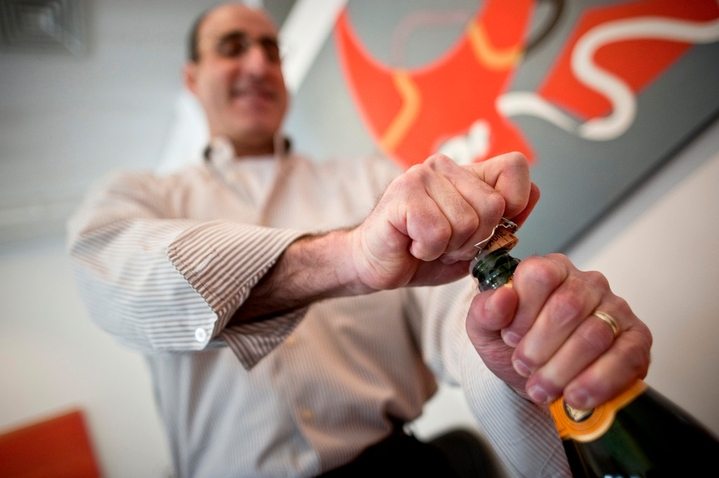 Gary Wartels from Skyview Wine & Spirits pops open a bottole of champagne. North Riverdale comunity leaders, including KRVC's Tracy Shelton and Maria Khury of Community Board 8 got together for the opening of a new exhibit, Orange!, at the Elisa Contemporary Art
