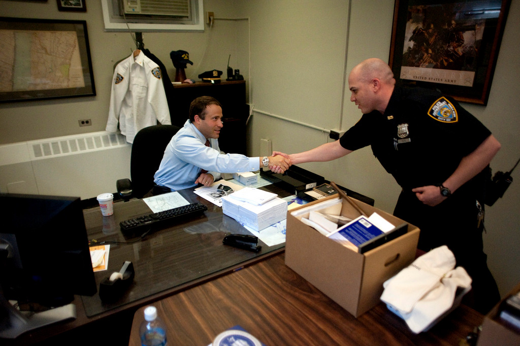 Police Officer Viltz, right, shakes Deputy Inspector Brandon del Pozo's hand on the Five-O commanding officer's last day, on May 27.