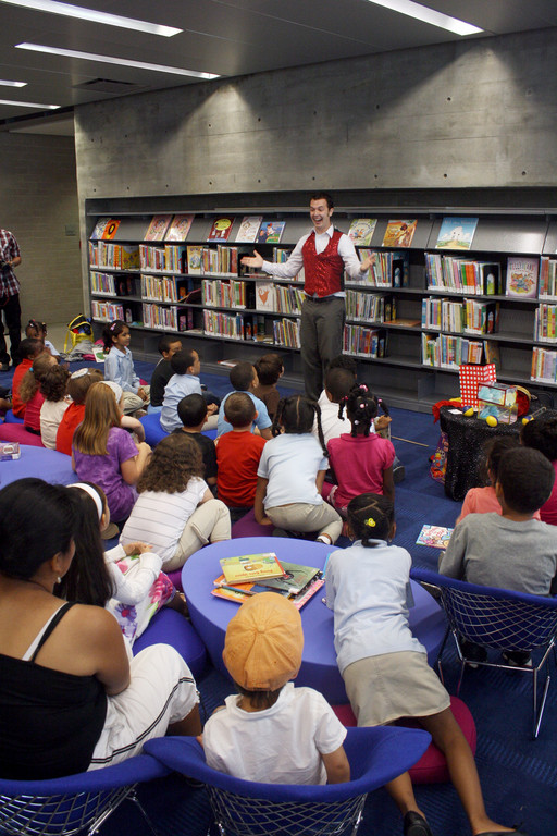 Festivities during the grand opening of the new Kingsbridge Public Library included a show by Magic Evan for a group of young children.