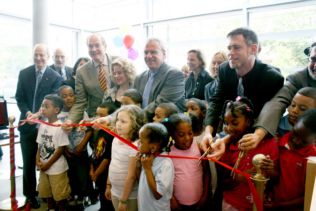 A group of distinguished guests and speakers, including state assemblyman Jeffrey Dinowitz, center, and first graders from the neighboring P.S. 37, cut the ribbon at the grand opening of the new Kingsbridge Public Library.