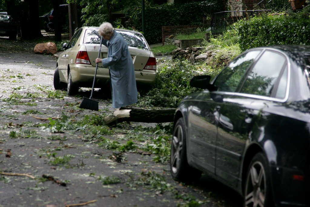 An elderly woman sweeps away the branches outside of her house.