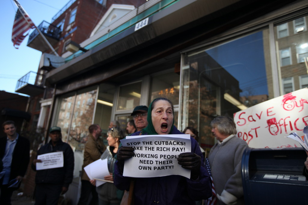 Rita Freed protests the potential closure of local post offices on Nov. 18, during the Senior Power