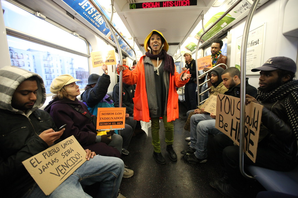 Protest organizer Nicole Carty, center, rallies local protesters with stories and grievances about the state of society in America on the subway from Fordham Road to Foley Park in Manhattan as part of the
