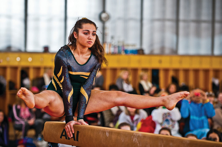 Shati Kumar, from Bronx High School of Science, straddles the balance beam on Feb. 12.