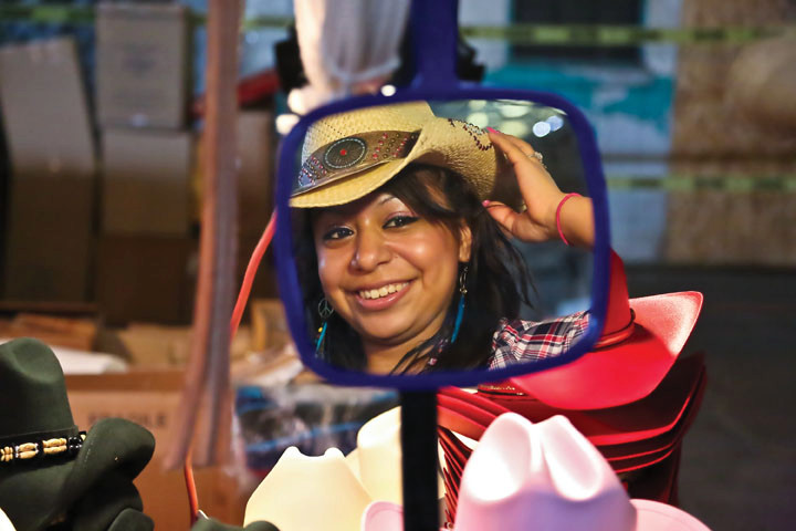 Daisy Herrear looks in the mirror to see if her cowboy hat has the right fit during an all-day family event at the Kingsbridge Armory that included a rodeo, wrestling and music.