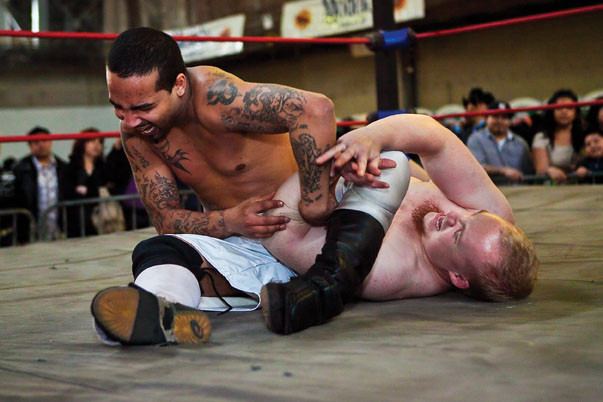 Tim Hughes puts Bronx resident and wrestler Rome in a submission hold.