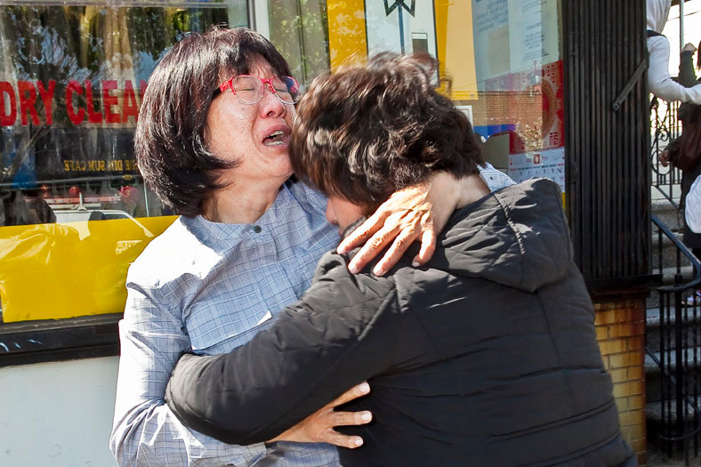 Ji Park (left) consoles Hyun Sup Yang, the mother of Hwang Yang, 26, who was shot and killed early this morning near the corner of West 232nd Street and Cambridge Avenue.