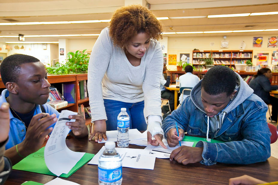Gilbert Nyantakyi, left, and Dejuane Nicholls, right, both freshman at New Vision Charter High School for Advance Math and SCience, receive living environment instruction on May 9 from Taina Roman, center, a tutor with Manhattan College Optimal Readiness Center.