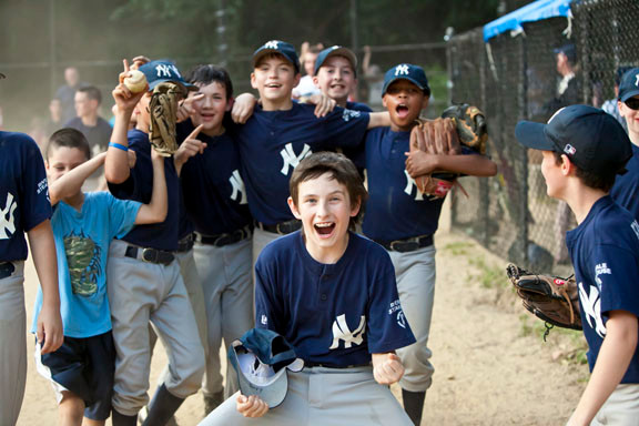 Yankees Lucas Ludgate, Rory Naughton, Brian Alberts, Brendan O'Sullivan, Justin Hill, left to right in background and Mac Hurry, foreground, celebrate their NRBL Major division championships at Kelly Field on June 20.