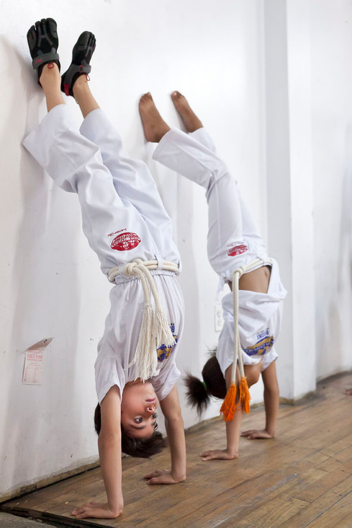 Jorge Ballestero and Ella Gonzalez do a head stand in the Saturday kids capoeira class at Church of the Mediator.