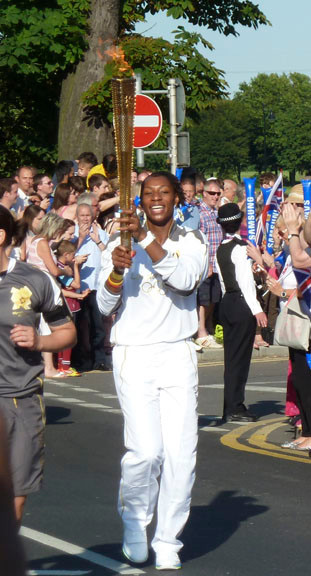 Rosalee Mason carries the Olympic torch in Bexley, a neighborhood in London, on July 22.