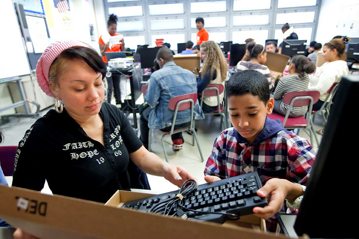 Angel Figuero, a sixth grader, sets up his new computer with help from his mother Zully Almonte at IN-Tech Academy, MS/HS 368, on Saturday.