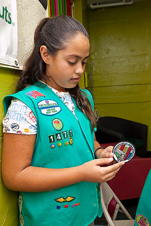 Jolee Caro, 10, from North Riverdale Troop 1477, shows off the winning patch that she designed.