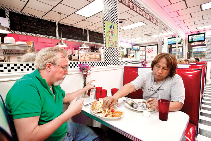Jerry McCarthy lets his friend Bill Gee try some of his fries at Tiny�s Diner on 3603 Riverdale Ave. on Sept. 28.