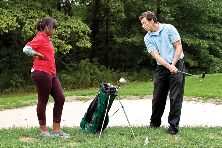 Coach Keith Mansfield mentors his student  Nichole Thomas, 15, from JFK during a golf match against Bronx Science on Sept. 20 at Mosholu Golf Course. Bronx Science wins the  game 4–1.