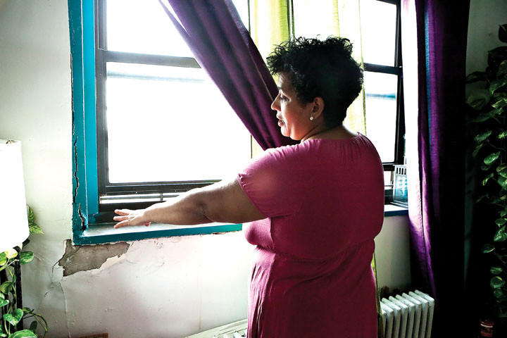 Griselda Herrera, 52, shows 'The Riverdale Press' a window sill on Sept. 20 that she says cracked after enduring years of leaks.