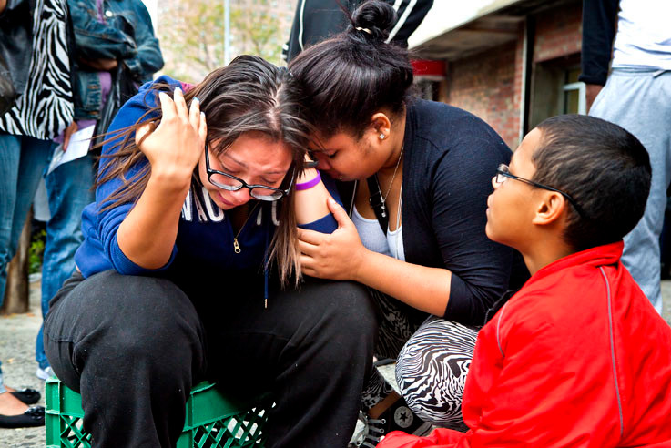 The morning after her brother Victor Maldonado was murdered, Nayiliana De Jesus, 15, at left, is consoled by her friend Samantha Franco, 18.