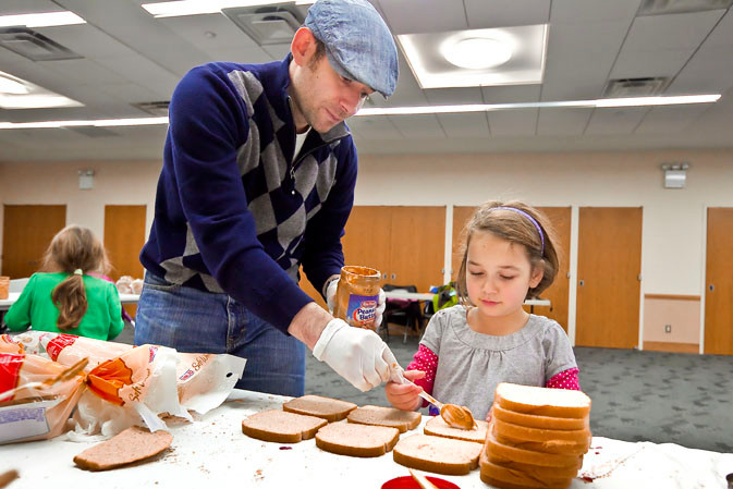 Michael Laskin helps his daughter Naomi, 6, make peanut butter sandwiches on Monday for people affected by Sandy. The event was organized and held at Hebrew Institute of Riverdale.