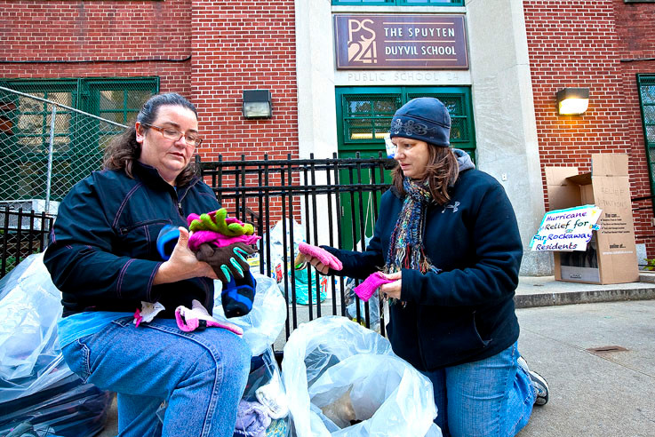 Liz Phelan and Carolyn Guarriello, outside of PS 24 on Monday, inspect lost and found items bound for Far Rockaway families in need.