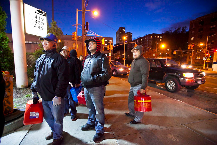 Alex Tavarez, Robert Peralta, Ramon Brito and others wait with jerrycans at the BP station on Broadway at West 230th Street and Riverdale Avenue on Monday night.