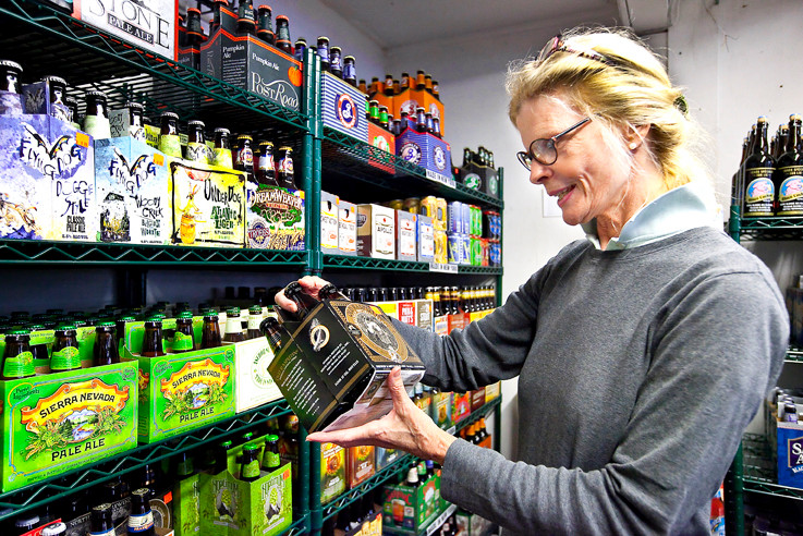 Carol Stewart of Broadway Beer & Soda explains some of the brews the store has on sale.