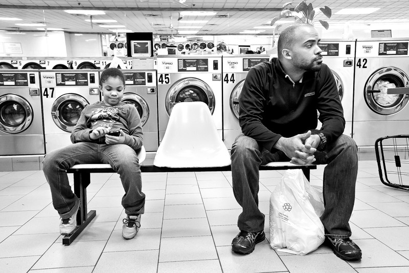 Adriana Alvarez, 7, waits with her dad, Andres Alvarez, at Broadway Laundromat on Oct. 20.
