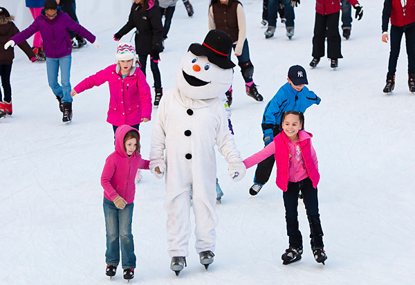 Frosty the Snowman, played by 'Riverdale Press' staffer Handal Gomez, skates with Ciara Elliot